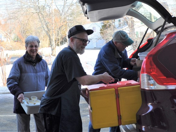 Volunteers loading coolers into car