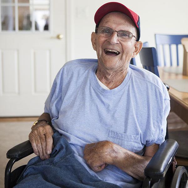 Elderly man in wheelchair smiling